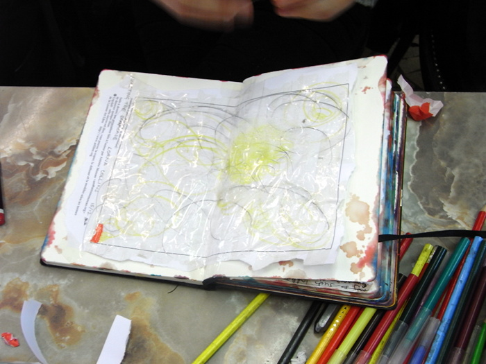 Lorna Collins drawing into her scrapbook